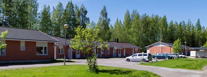 Kuva kiinteistön pihalta, jossa on rivitalo ja parkkipaikka